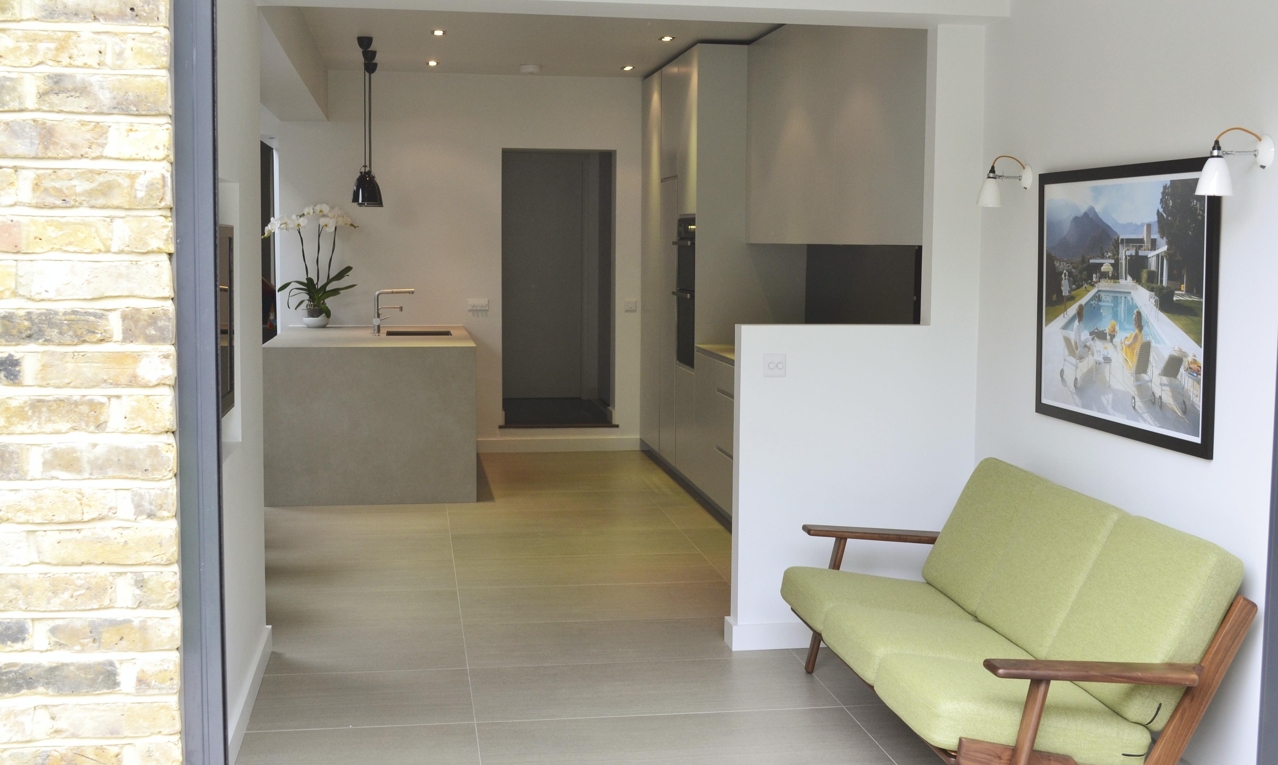 Green sofa in a contemporary white kitchen
