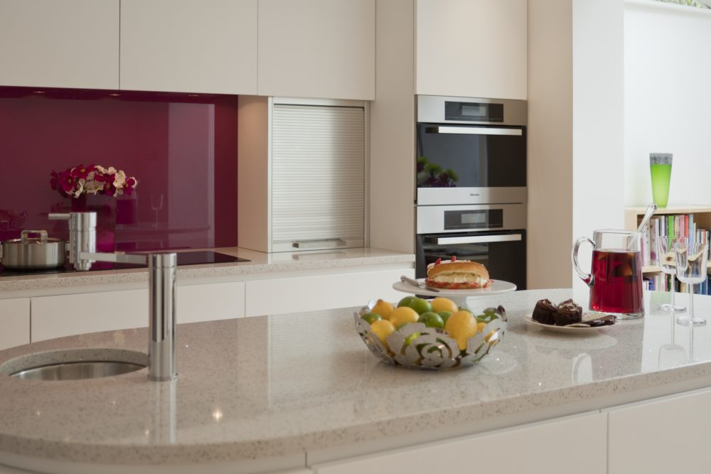 Clean contemporary family kitchen with feature raspberry glass splashback.