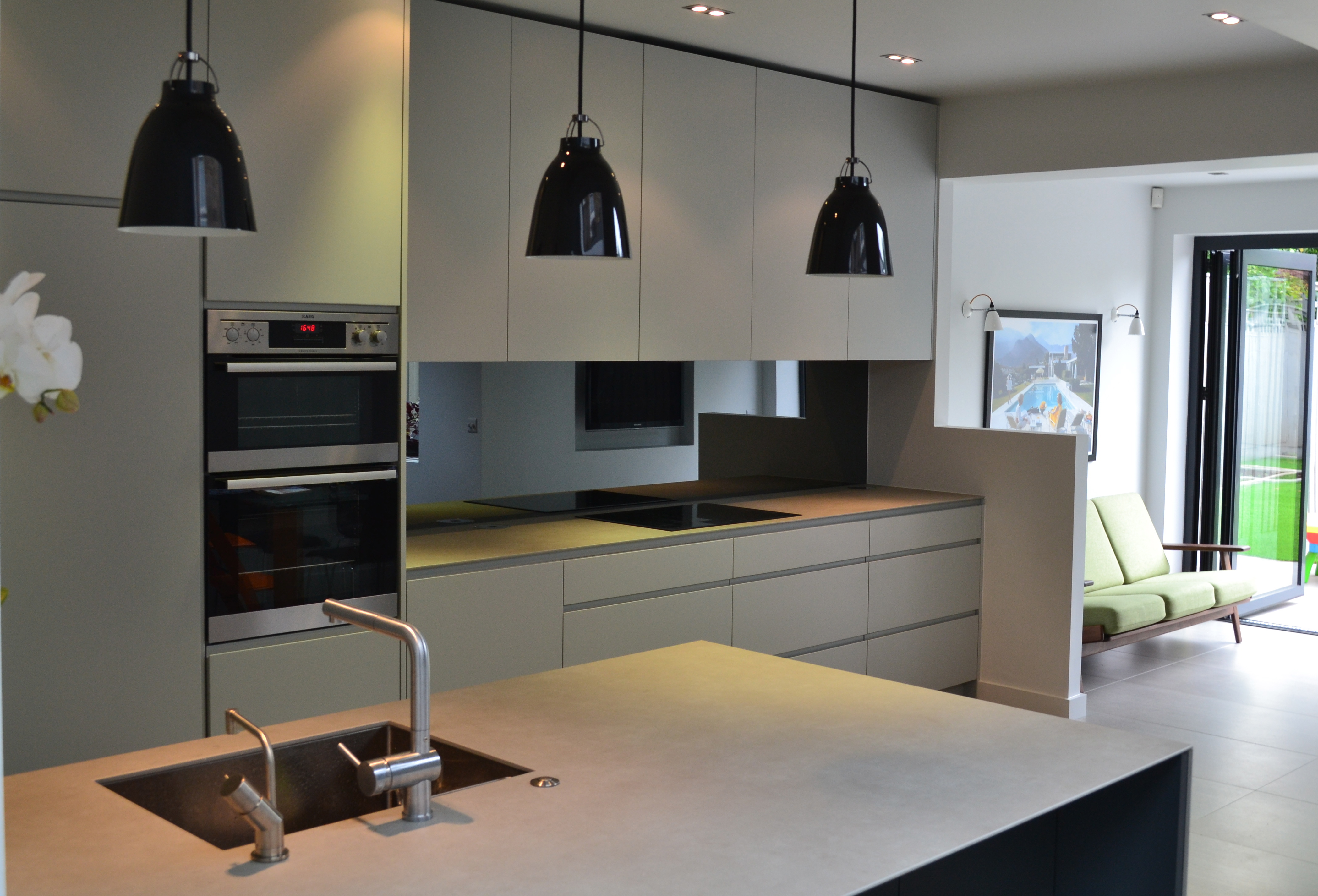 View of kitchen island and wall units with pendant lamps