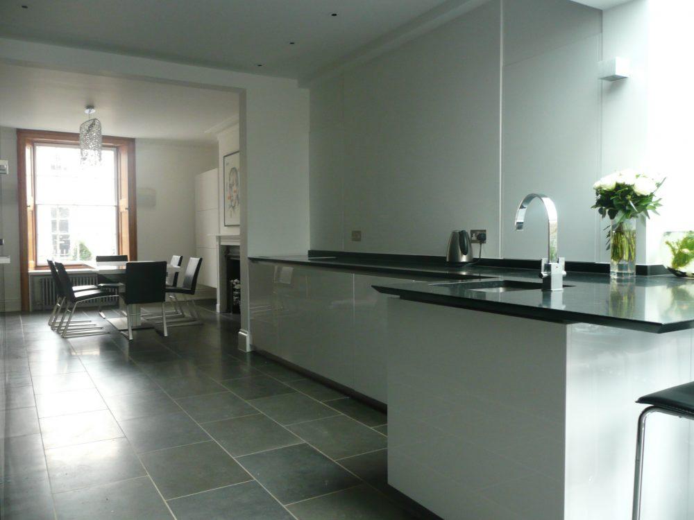 Minimal monochrome kitchen dining room with sleek white units and black worktops.