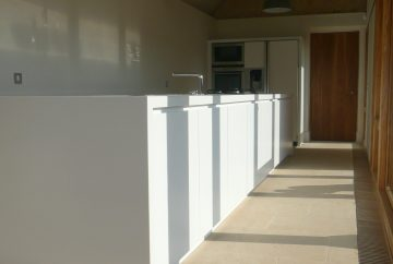 Run of white kitchen cupboards in timber framed barn conversion.