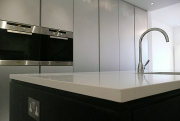 Side view of minimal design kitchen island with white worktop and black cabinet. White wall cupboards and fitted cooker in background.